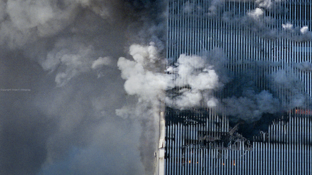 Smoke and fire billow out of a gaping hole in the WTC North Tower after two commercial jetplanes crashes into each of twin towers of the World Trade Center in a coordinated terror attack orchestrated by Usama Bin Laden.