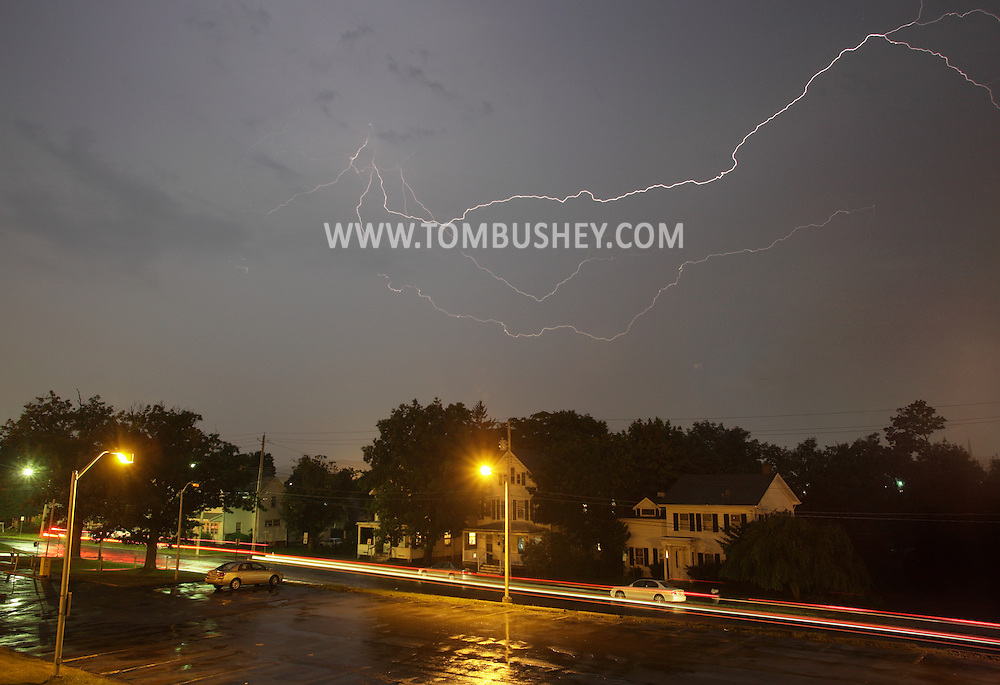 Middletown, NY - Lightning streaks across the sky above a street and houses during a summer thunderstorm on the night of July 25, 2009. The streaks of light are from passing cars during the long exposure.