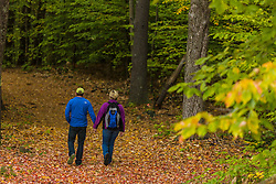 A couple walking on a woods road in Barrington, New Hampshire. Fall.