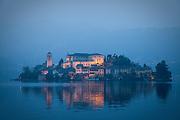 The island monastery of Isola San Giulio on Lake Orta at dusk, from Orta San Giulio, Piedmont, Italy.