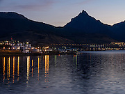 "At dawn, lights reflect in the Beagle Channel at the Port of Ushuaia, capital city of Tierra del Fuego Province, Argentina, South America. As the port closest to Antarctica (which is located 400 miles across the Drake Passage), Ushuaia hosts most of the cruise ships that visit the southernmost continent. Argentina claims Ushuaia is the ""southernmost city in the world"" (although the smaller Chilean town of Puerto Williams lies further south). The Martial Mountains provide skiing and hiking above town."