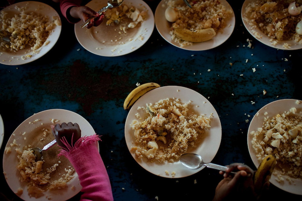 Children, some of them HIV positive, receive free lunch donated by the Italian Community of Saint'Egidio near a school in a poor neighborhood in Maputo, Mozambique, Aug. 2009. The Italian ngo, which has the first center focused on prevention of mother to child HIV transmission, is also fighting malnutrition by providing food to poor children. Malnutrition is the main underlying cause contributing to the high level of child mortality.