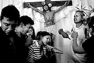 Family and friends mourn the death of Maximo during a Catholic rosary vigil before his burial. Maximo was fatally shot outside of a family home in Belen on April 24, 2008.