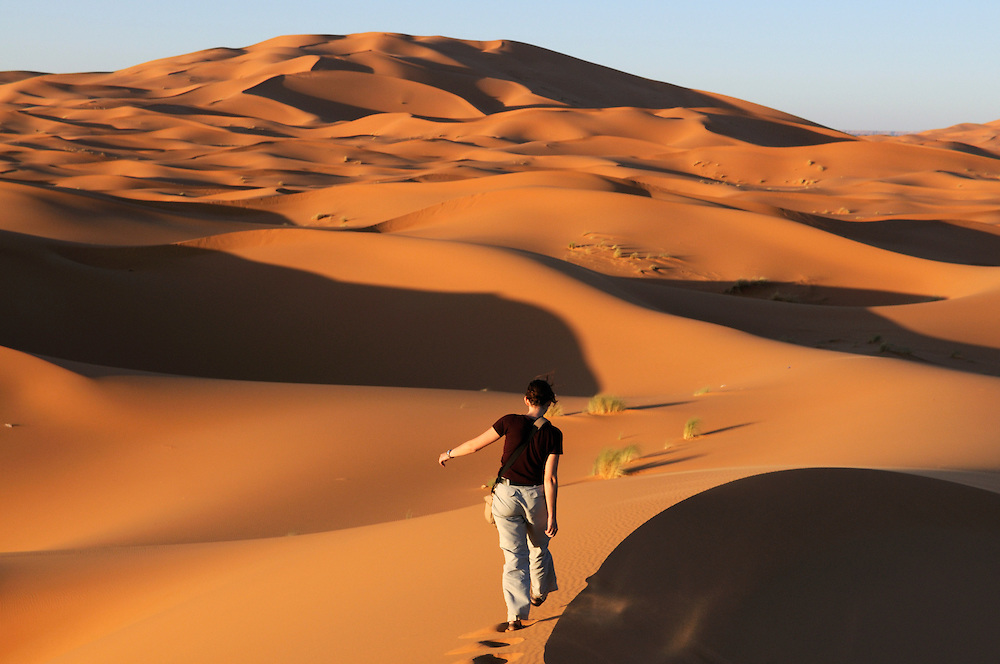 The back of a young woman, who is walking at the dunes of a sand desert. Merzouga. Morocco. Africa.