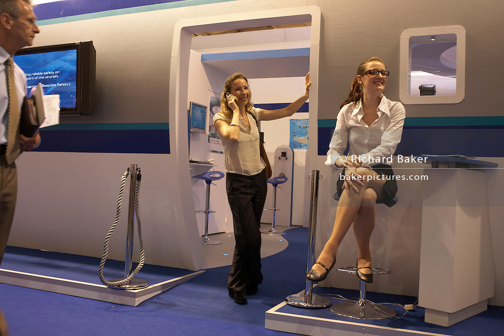 A young lady perches on a stool outside an aircraft cabin mock-up during the Paris Air Show exhibition at Le Bourget airfield
