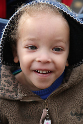 Toddler in coat smiling, dual heritage, boy
