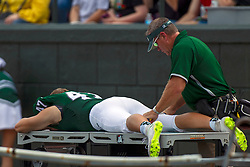BLOOMINGTON, IL - September 28:  A Titan gets his leg muscles rolled by the IWU trainer during a college football game between the IWU Titans and the Augustana Vikings on September 28 2019 at Wilder Field in Tucci Stadium in Bloomington, IL. (Photo by Alan Look)