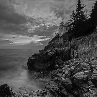 Black and White New England photography of the iconic Bass Harbor Head Light located on Mount Desert Island within Maine Acadia National Park on the southeast corner of MDI. The lighthouse towers over the swirling Atlantic Ocean and seacoast, marking the entrance to Bass Harbor and Blue Hill Bay. It is one of the most iconic scenery of Acadia NP as Bass Harbor Light is dramatically located on the edge of rugged cliffs.<br />