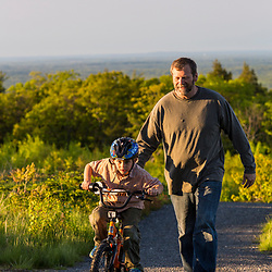 A man helps his young son ride a bike near the summit of Mount Agamenticus in York, Maine.