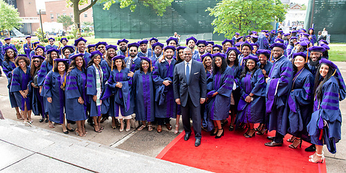 A large group of graduating Howard University students with 2019 commencement speaker Kasim Reed in the center.