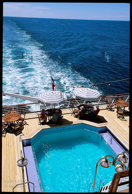 Passengers sit by pool watching the wake of the cruise ship Clipper Odyssey in the azure waters of the South Pacific; New Zealand.