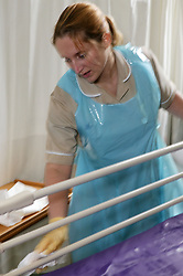 Auxiliary Nurse preparing Hospital Ward bed for new patient,