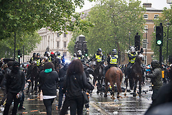 © Licensed to London News Pictures. 06/06/2020. London, UK. Police on horseback clash with protesters as they gather in Westminster, central London to take part in a Black Lives Matter demonstration over the killing of African American George Floyd. The death of George Floyd, who died after being restrained by a police officer In Minneapolis, Minnesota, caused widespread rioting and looting across the USA. Photo credit: Ben Cawthra/LNP