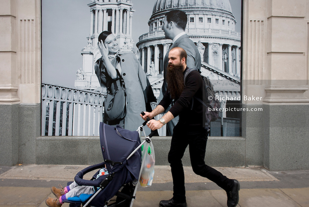 A man pushes a child's buggy past a fashion poster showing a fashion boy and girl and St Paul's Cathedral.