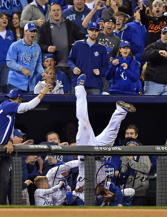 Kansas City Royals third baseman Mike Moustakas falls into fans in the stands as he catches a foul pop up hit by Baltimore Orioles center fielder Adam Jones (not pictured) during the sixth inning in game three of the 2014 ALCS playoff baseball game at Kauffman Stadium.