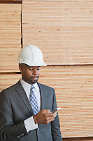 African American male engineer using cell phone with stacked wooden planks in background