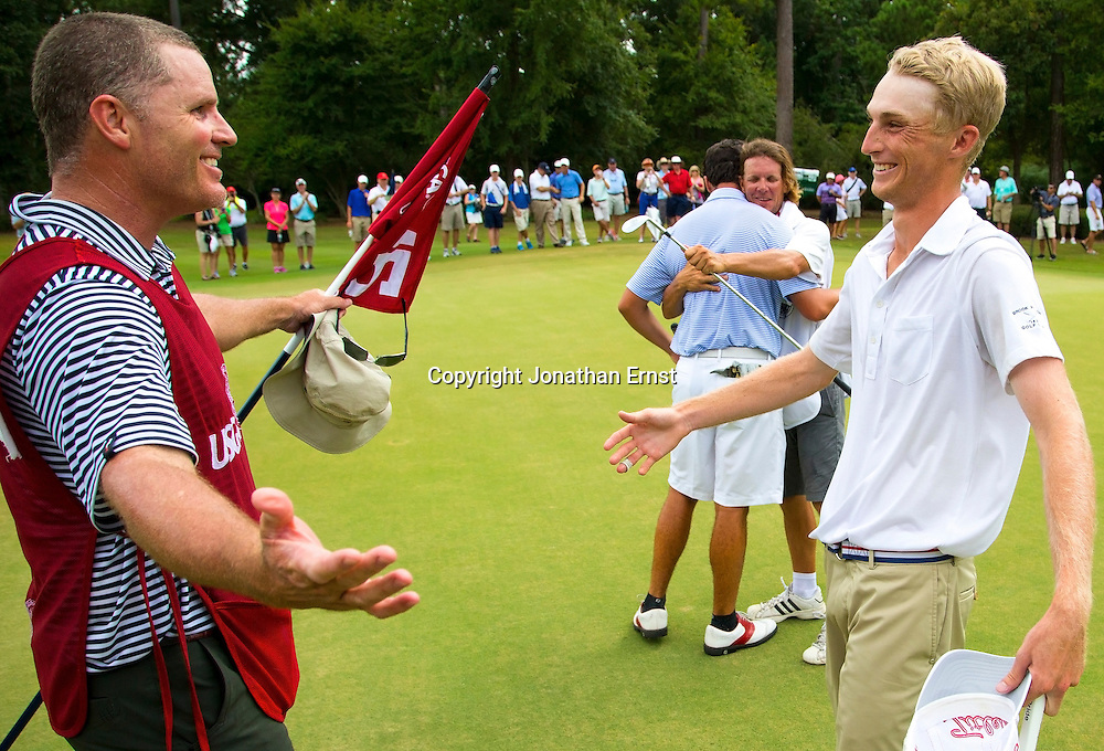 William Zalatoris (R) and his caddie celebrate his victory over Davis Riley on the 15th green on the 33rd hole of the final round of match play at the 2014 U.S. Junior Amateur at The Club at Carlton Woods in The Woodlands, Texas.