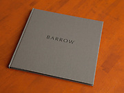 Barrow 34 pages, features twelve black and white and four color images, archival pigment printing on Moab Entrada Bright, Hardbound in slipcase. Edition of ten with two artist's proofs. Signed and numbered. First copy $450, with price increases as edition is sold.<br /> <br /> From the Introduction:<br /> Barrow, Alaska occupies the northern most point of land in the United States, pressed hard upon the Chukchi Sea and the Arctic Ocean, some 330 miles north of the Arctic Circle. The native Inupiat people have lived in Barrow for four thousand years and continue to practice traditional ways of life, including whaling and subsistence hunting. As there are no roads in, the city is accessible only by air for 10 months of the year and is arguably the most isolated city in the country. •<br /> <br /> I've had the good fortune to visit Barrow twice on assignments and on this most recent trip I scheduled time to spend making photographs of this unique American place. •<br /> <br /> It was March and while the sun was up for eight or so hours, it's low angle made for beautiful light, when not obscured by persistent ice fog. Temperatures ranged from a high of -11° F to -30° F with a constant wind coming off the ocean, making for somewhat difficult conditions. Batteries stopped working and the extreme temperature even affected my normally very fine grain film. •<br /> <br /> Knowing that producing a meaningful document of the people of Barrow would be impossible in my short time, I chose to focus on the landscape. As I walked the streets, vigilant for polar bears, I became entranced by the stark, yet subtle textures of the largely featureless tundra, and how it merged with the frozen ocean; by the low angled light, and the often whimsical sculptural forms, that I encountered. These are the resulting photographs.