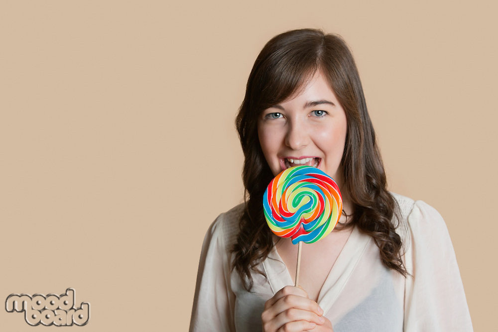 Portrait of a beautiful young woman with lollipop over colored background