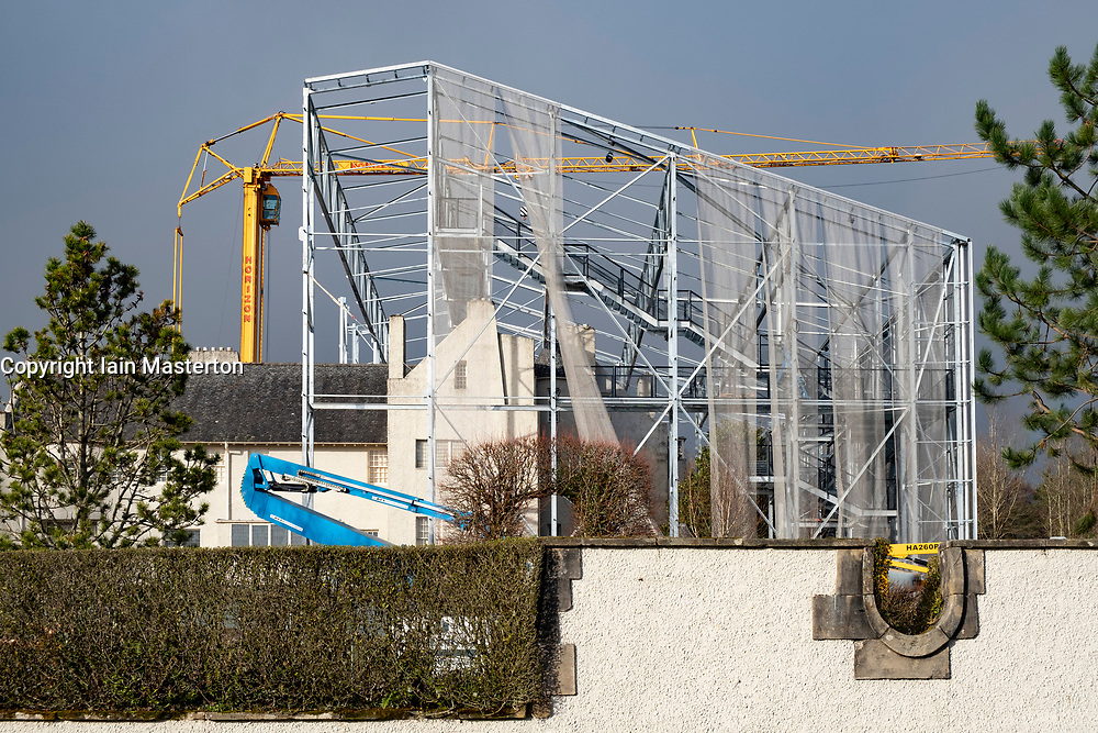 """Hill House in Helensburgh during construction of  """"box"""" project to assist drying of the building exterior. Consists of a protective steel frame structure covered in chainmail mesh, featuring walkways around and over the top of the house. Scotland, UK."""