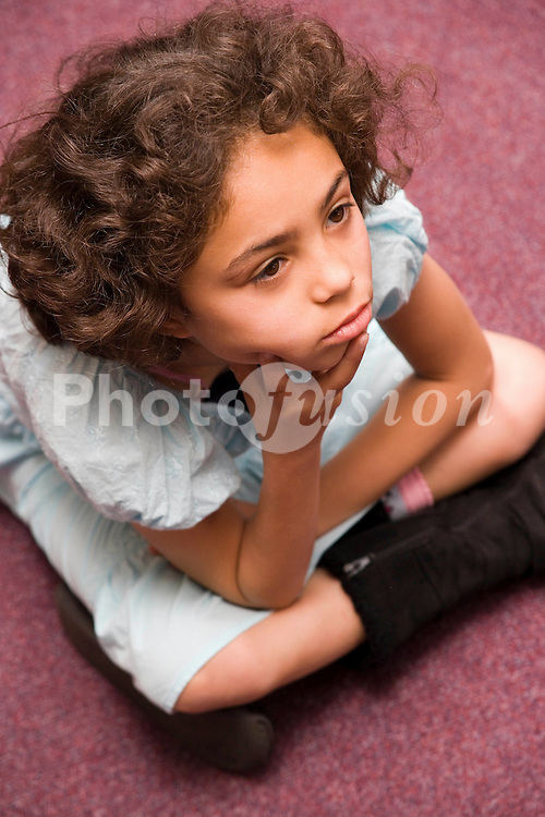 Girl sitting on floor in classroom looking thoughtful,