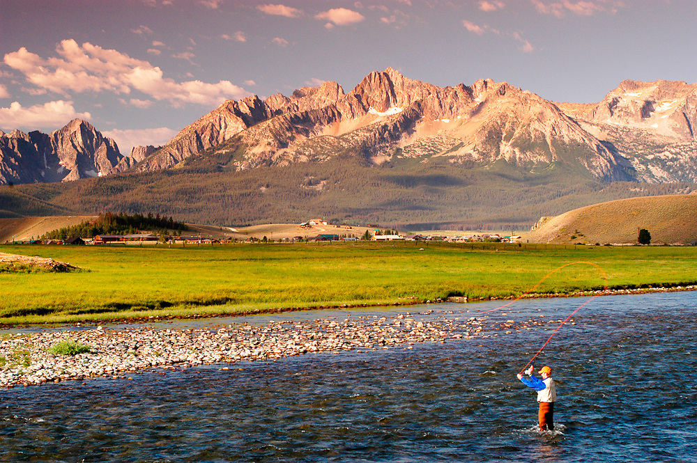 USA. Idaho. Stanley. Salmon River. Fly fisherman casting with Sawtooth Mountain peaks beyond in summer. MR