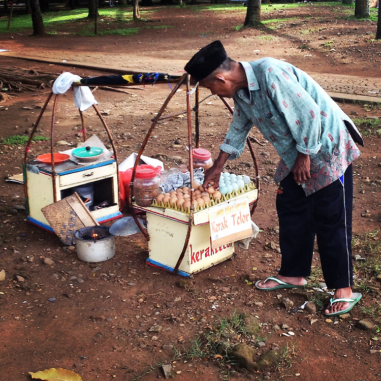Kerak Telor food vendor.  Kerak Telor is a Betawi traditional spicy omelette snack.  It is made from glutinous rice cooked with egg and served with serundeng (fried shredded coconut), fried shallots and dried shrimp as topping.