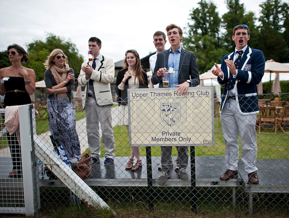 © London News Pictures. 03/07/2012.  Henley-on-Thames, UK.  Spectators wearing rowing club colours watching a race on Day one of Henley Royal Regatta on the River Thames at Henley-on-Thames, Oxfordshire on July 03, 2013. Photo credit: Ben Cawthra/LNP