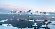 Evening view from Useful Island towards Graham Land, Antarctic Peninsula, Antarctica. Do note the many Gentoo penguin colonies in the foreground
