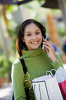 Woman with Shopping Bags Using Cell Phone