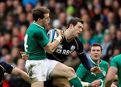 09.02.2013 Edinburgh, Scotland.   Ireland's Criag Gilroy feels the tackle of Scotland's Tim Visser  during the RBS Six Nations Championship match between Scotland and Ireland, from Murrayfield Stadium.