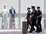 Two mannequins, hoping to avoid detection, stay completely still while the unsuspecting cops walk by on Liberty Street in downtown Manhattan