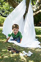 Young boy in back yard crawling out of tent made of bed sheet portrait