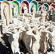 White plaster or cement Goddess statuettes stand on sale on the forecourt of a garden art business in an Athens suberb, Marathonas Avenue - the original Marathon route of 490 BC. The mostly female figurines are in various poses but are all nudes and are in various gestures of a classical heroic style. Those in the foreground have their arms at the heads and moulded breasts and bodies to show the perfect female form while further to the back are male Gods placed on plinths and in recesses. The 29th modern Olympic circus came home to Greece in 2004 and the birthplace of athletics and the Olympic ideal, amid the woodland of ancient Olympia where for 1,100 continuous years, the ancients held their pagan festival of sport and debauchery.