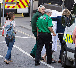 © London News Pictures. 09/08/2013. London, UK. Katie Gee (right) covered in a white sheet being taken into Chelsea and Westminster Hospital followed by her mother Nicky Gee (far left) after arriving back in the UK. Katie Gee and her friend Kirstie Trup were victims of an acid attack while working as charity volunteers in in Zanzibar. Photo credit : Ben Cawthra/LNP