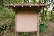 a notice board in the woods with a funny face drawn on it