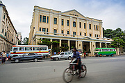 07 JUNE 2014 - YANGON, MYANMAR: A man rides his bike past the Strand Hotel. The Strand Hotel in Yangon is now one of the most expensive hotels in Yangon. It opened in its current location in 1901 and is one of the jewels of Yangon's colonial architecture. Yangon has the highest concentration of colonial style buildings still standing in Asia. Efforts are being made to preserve the buildings but many are in poor condition and not salvageable.    PHOTO BY JACK KURTZ