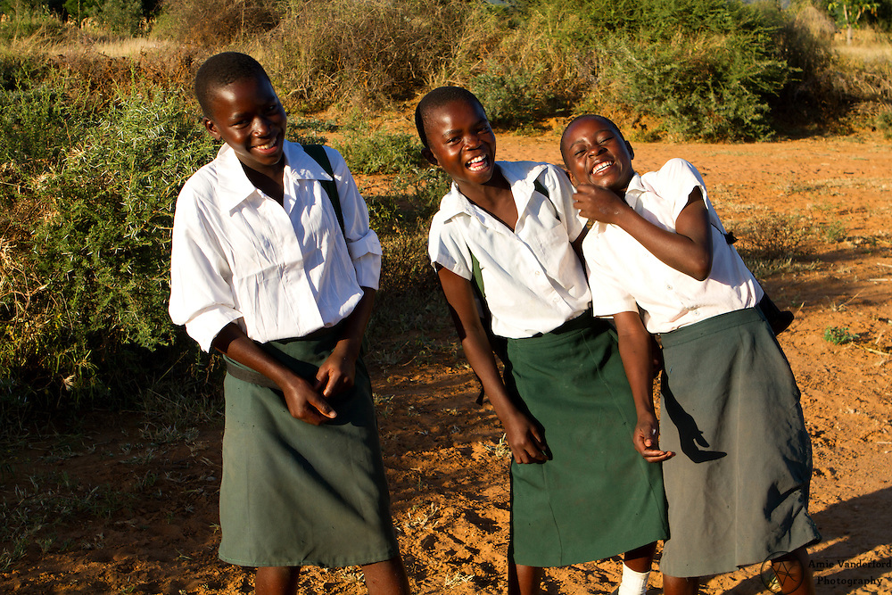 Young African girls stop to talk and laugh with me on their way to school.