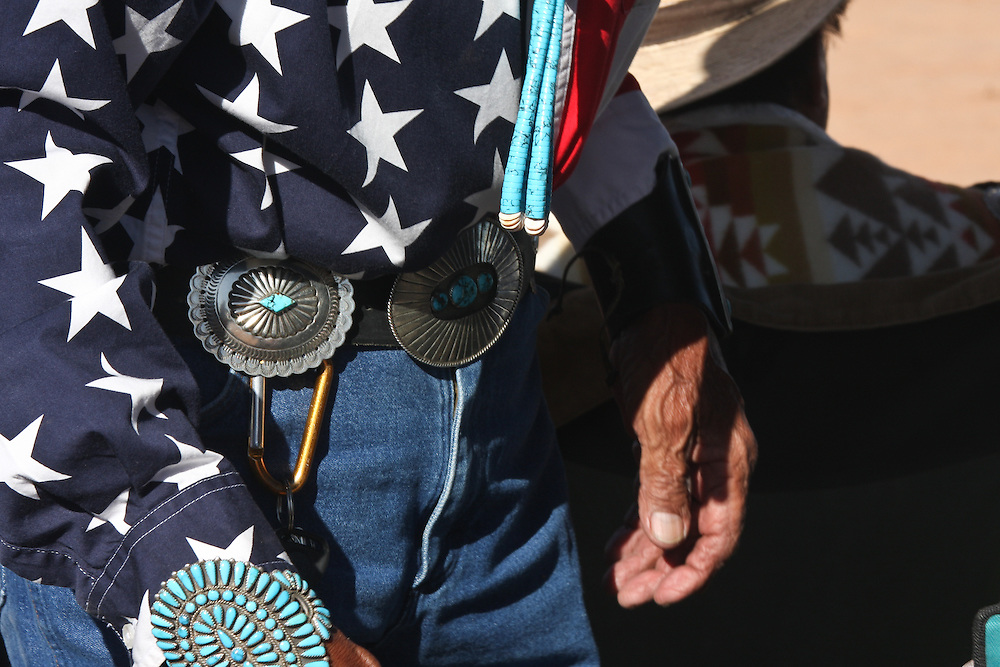 An old Navajo man, dressed in a stars and strpes shirt, wearing traditonal jewelry, is taking part at a Song and Dance performance in Window Rock, Arizona  at the Navajo Nation Fair.