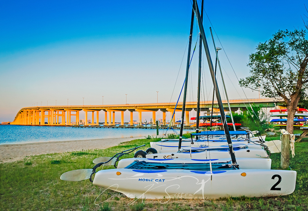 The sun rises over Hobie Cat sailing catamarans lined up along Front Beach at Ocean Springs Yacht Club, Aug. 26, 2014, in Ocean Springs, Mississippi. The yacht club was founded in 1969. The original clubhouse was destroyed by Hurricane Katrina in 2005 and rebuilt. (Photo by Carmen K. Sisson/Cloudybright)