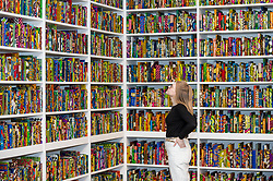 "© Licensed to London News Pictures. 08/04/2019. LONDON, UK.  A staff member views British-Nigerian artist Yinka Shonibare's artwork ""The British Library"", 2014, which has been acquired by Tate Modern.  Comprising 6,328 books, covered in wax fabric and gold foil, 2,700 books have the names of first or second generation immigrants to Britain on the spine.  Photo credit: Stephen Chung/LNP"