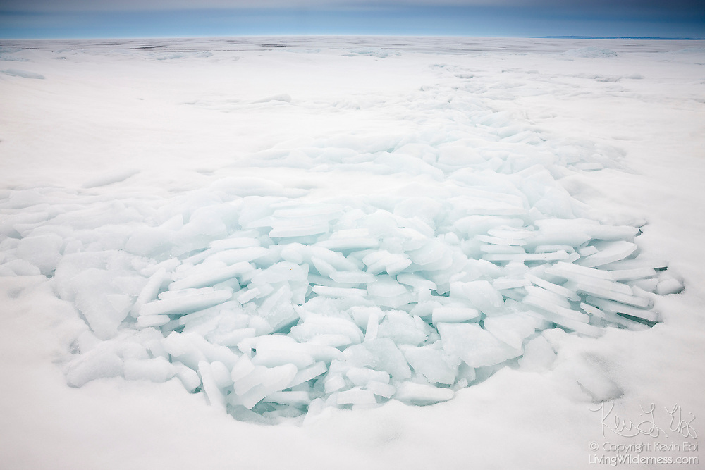 Sheets of ice, piled high by strong winds, sit atop frozen Lake Superior in Pendills Bay, Michigan. As the great lakes begin to freeze, winds often blow the ice into piles, creating unique ice sculptures.