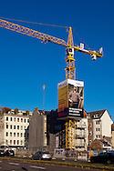 Europa, Deutschland, Nordrhein-Westfalen, Koeln, Baustelle, Kran der Firma Wolff & Mueller mit Werbeplakaten. Der sogenannte Skycrane ist eine vierseitige, quaderfoermige Verkleidung des Baukrans. Die angebrachten Werbeplakate sind hinterbeleuchtet und ergeben eine Gesamtflaeche von ca. 290 Quadratmetern. ..Europe, Germany, North Rhine-Westphalia, Cologne, construction site, crane of the company Wolff & Mueller with  advertisement. The so called Skycrane is a cuboidal casing of the crane. The mounted billboards are lit behind and produce an area of approximately 290 square meters.