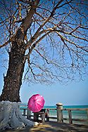 Pink umbrella hides a person sitting on a bench overlooking the turquoise waters of Nha Trang beach, Vietnam, Southeast Asia