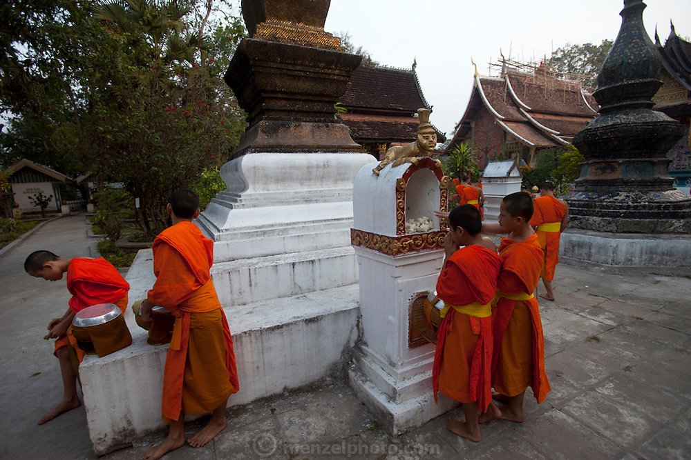 "Luang Prabang, Laos. Every morning at dawn, barefoot Buddhist monks and novices in orange robes walk down the streets collecting food alms from devout, kneeling Buddhists. They then return to their temples (also known as ""wats"") and eat together. This procession is called Tak Bat, or Making Merit. Monks leaving offerings of sticky rice at their temple, Wat Xiengthong."