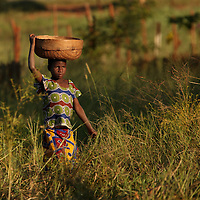 A young boy carries a basket on his head while walking through a field toward a road-side market in the Manica Province in Mozambique, Africa.