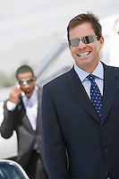 Mid-adult businessman in sunglasses smiling.