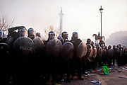 Riot police officers stand firm in Trafalgar Square at the height of the Poll Tax Riot on 31st March 1990, in Westminster, London, England. Angry crowds, demonstrating against Margaret Thatcher's local authority tax, stormed the Whitehall area and then London's West End, starting fires and overturning cars, looting stores up Charing Cross Road and St Martin's Lane. The anti-poll tax rally in central London erupted into the worst riots seen in the city for a century. Forty-five police officers were among the 113 people injured as well as 20 police horses. 340 people were arrested. (Photo by Richard Baker / In Pictures via Getty Images)