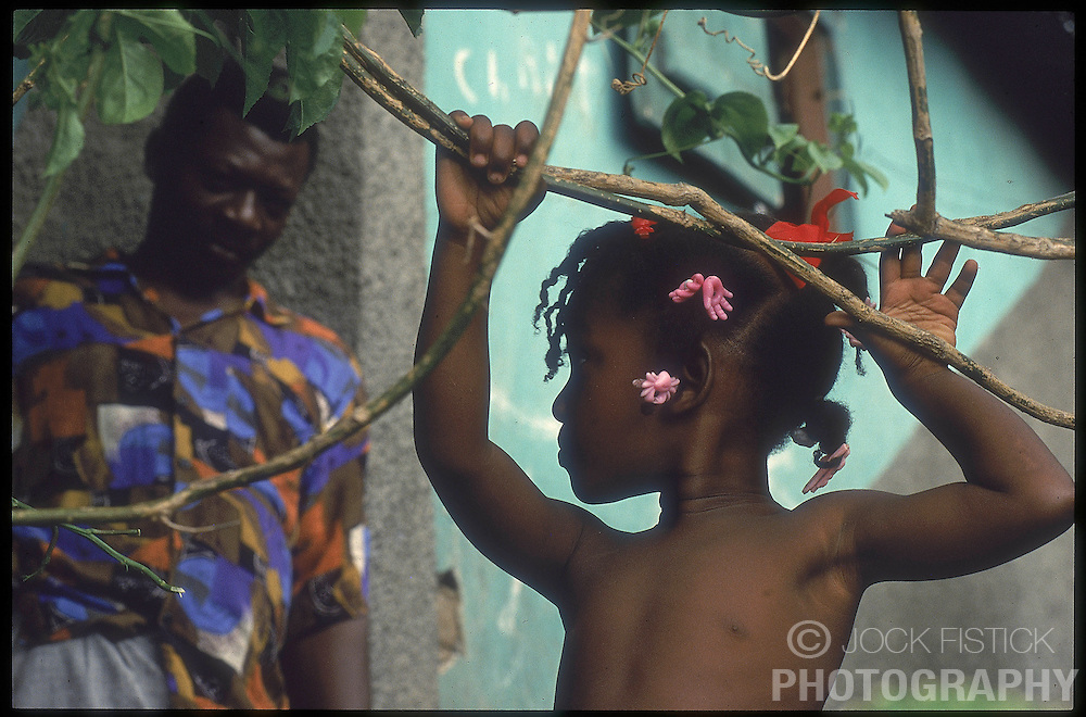 CAP HAITIEN, HAITI - Jean Noel Jackson once ran his own business in Cap Haitien, and was able to support his mother, wife and four children. But all was lost when civil war broke out. Now, as he watches his daughter Michelle play, he wonders where their next meal will come from. (PHOTO © JOCK FISTICK)....
