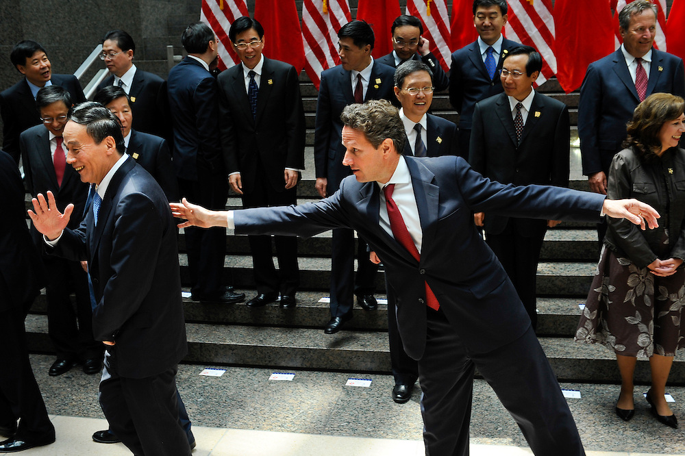 U.S. Treasury Secretary Timothy Geithner (R) attempts to redirect Chinese Vice Premier Wang Qishan to the exit after a family photo as they gather for the first joint meeting of the US-China Strategic and Economic Dialogue in Washington.